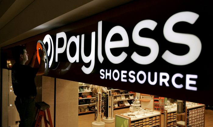 A worker puts the finishing touches on a sign unveiling the company's new look at a Payless Shoesource store at a mall in Independence, Mo., on May 18, 2006. (Charlie Riedel/AP)