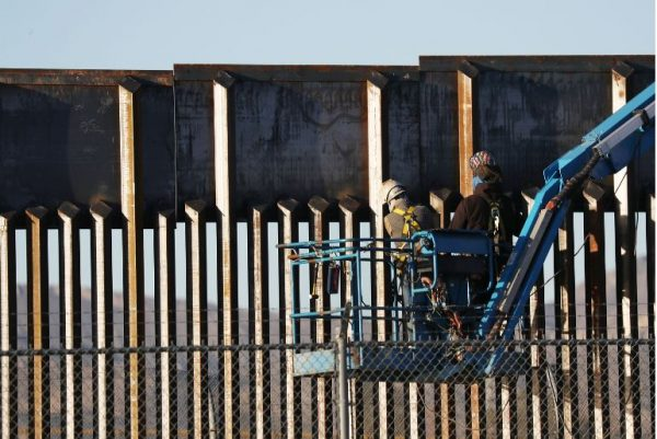 People work on the U.S./ Mexican border wall