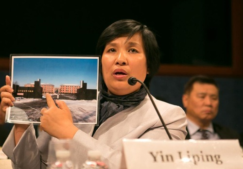 Falun Dafa practitioner Yin Liping shows a photo of Masanjia Labour Camp to congressional representatives at a hearing on Capitol Hill on April 14, 2016. Yin was a victim of torture and gang rape while incarcerated at Masanjia. (Minghui.org)