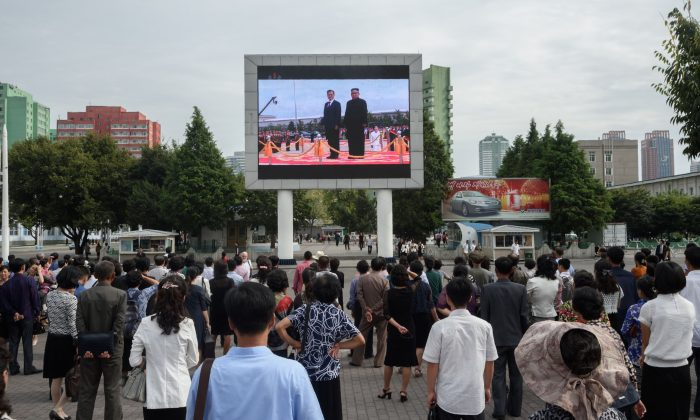Bystanders watch a news broadcast showing images of a summit meeting between North Korea's leader Kim Jong Un and South Korea's president Moon Jae-in on a public television screen in Pyongyang on Sept. 19, 2018. (Kim Won Jin/AFP/Getty Images)