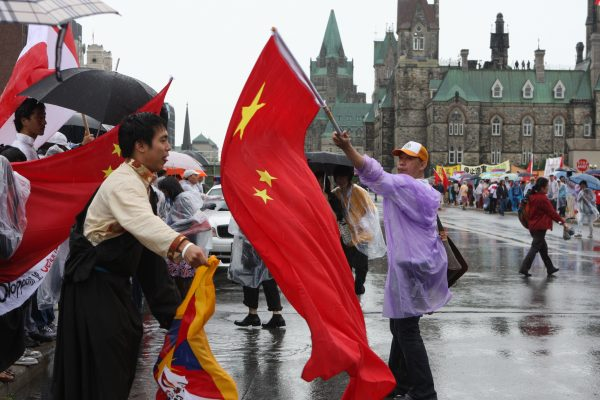 A man with a large Chinese flag blocks a Tibetan protester