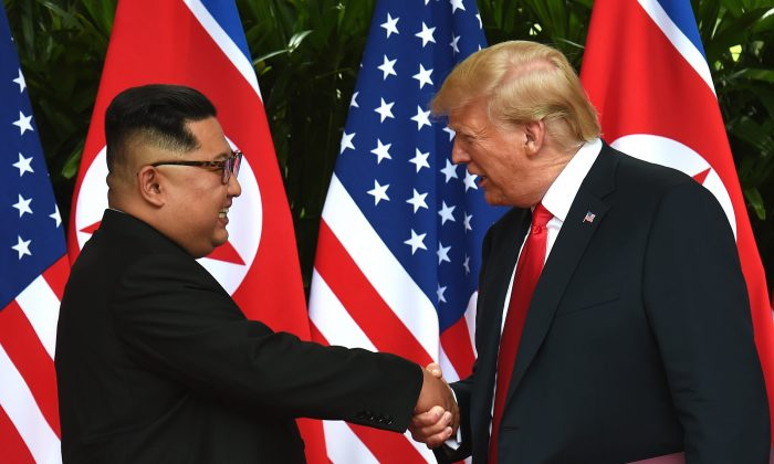 President Donald Trump shakes hands with North Korea's leader Kim Jong Un after a signing ceremony at the end of their U.S.–North Korea summit on Sentosa Island, Singapore, on June 12, 2018. (ANTHONY WALLACE/AFP/Getty Images)