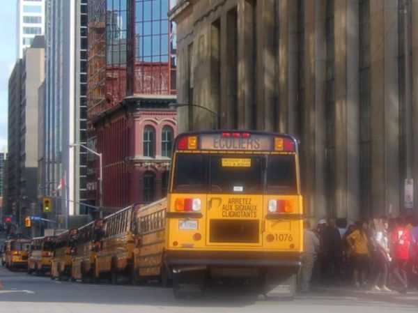 A long line of school buses parked near Parliament Hill.