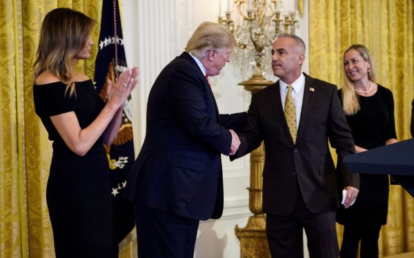Andrew Pollack (C), father of Stoneman Douglas High School mass shooting victim Meadow Pollack, shakes hands with President Donald Trump (2nd L) as first lady Melania Trump (L), Julie Phillips Pollack (2nd R), and Hunter Pollack (R) watch during a Hanukkah reception at the White House