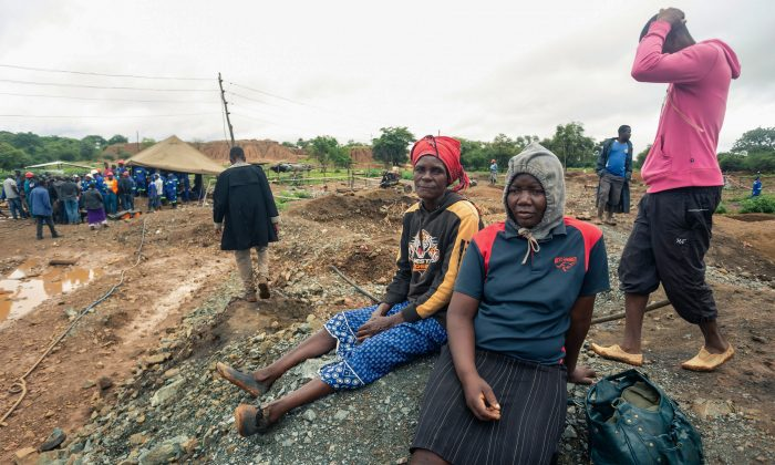 Relatives of deceased artisanal miners sit during an ongoing rescue and recovery operation at the flooded Cricket gold mine near Kadoma, Zimbabwe, on Feb. 17, 2019. (Jekesai Njikizana/AFP/Getty Images)