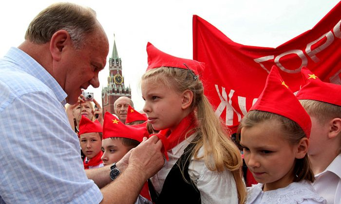 Gennady Zyuganov, leader of the Russian Communist Party ties red scarves around childrens' necks, symbolizing their initiation into the Young Pioneer Youth communist group created in the Soviet Union for children 10–14 years old, in Moscow's Red Qquare in this file photo. (Alexey SAZONOV/AFP/Getty Images)
