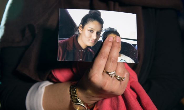 Renu Begum, eldest sister of Shamima Begum, 15, holds her sister's photo as she is interviewed by the media at New Scotland Yard, in London on Feb. 22, 2015. (Laura Lean - WPA Pool/Getty Images)