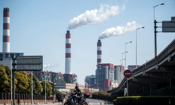 A man rides his scooter near the Shanghai Waigaoqiao Power Generator Company coal power plant in Shanghai on March 6, 2017. (JOHANNES EISELE/AFP/Getty Images)