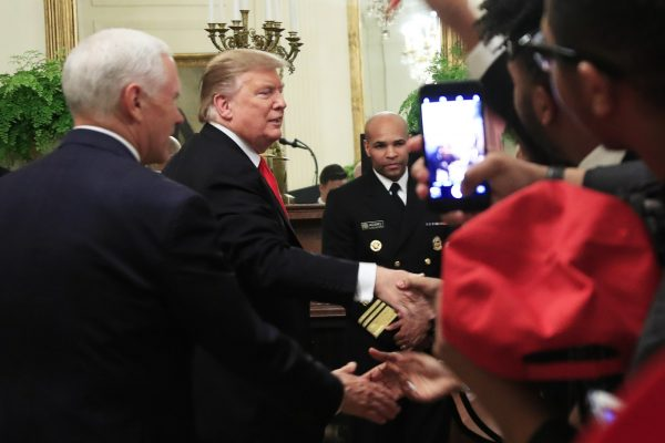 President Donald Trump with Vice President Mike Pence shakes hands with Surgeon General Jerome Adams