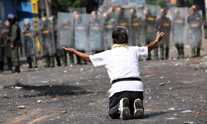 A demonstrator kneels down in front of security forces in Urena, Venezuela, on Feb. 23, 2019. (Andres Martinez Casares/Reuters)