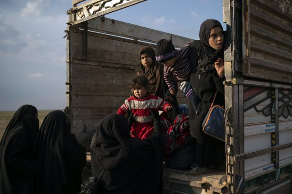 Women and children exit the back of a truck, part of a convoy evacuating hundreds out of the last territory held by Islamic