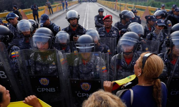 Venezuela's opposition supporters demand to cross the border line between Colombia and Venezuela at Simon Bolivar bridge as Venezuela's security forces stand in the border line blocking their way in the outskirts of Cucuta, Colombia, on Feb. 23, 2019. (Edgard Garrido/Reuters)