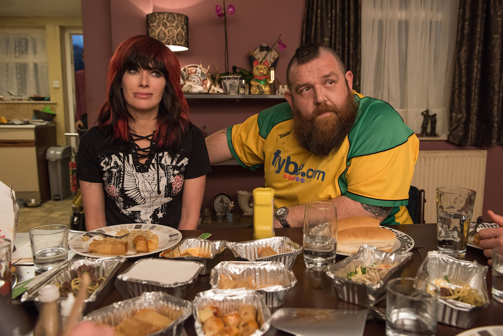 man and wife wrestlers sit at dinner table