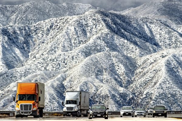 Mountains are blanketed with snow as traffic makes its way slowly
