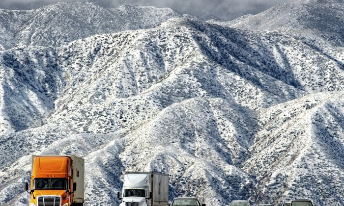 Mountains are blanketed with snow as traffic makes its way slowly through Cajon Pass on the I-15 near Hwy 138 in Phelan, Calif., on Feb. 21, 2019. (Watchara Phomicinda/The Orange County Register via AP)