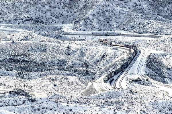 A train rolls along the snow covered hills in the Cajon Pass near Highway 138