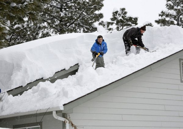 Homeowner Kevin Ireland, right, and Tommy Tokarczyk clear several feet of snow off