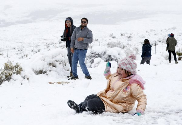 Valentina Gonzalez, 7, laughs after falling during a snowball fight
