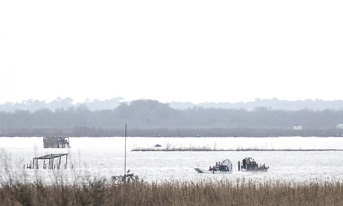 Emergency personnel work at the scene of a plane crash site in Trinity Bay in Anahuac, Texas on Feb. 23, 2019. (Brett Coomer/Houston Chronicle via AP)