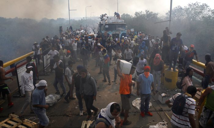 Opposition supporters unload humanitarian aid from a truck that was sent on fire after clashes between opposition supporters and Venezuela's security forces at Francisco de Paula Santander bridge on the border line between Colombia and Venezuela as seen from Cucuta, Colombia, Feb. 23, 2019. (Marco Bello/Reuters)