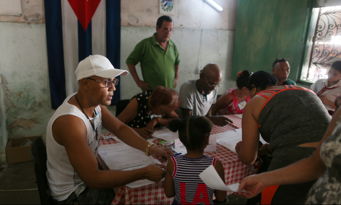 Election officials check the documents of a voter at a polling station during a constitutional referendum in Havana, Cuba, Feb. 24, 2019. (Fernando Medina/Reuters)