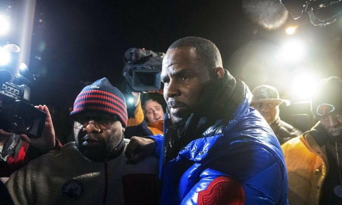 R. Kelly surrenders to authorities at Chicago First District police station, on Feb. 22, 2019. R&B star R. Kelly was taken into custody after arriving Friday night at a Chicago police precinct, hours after authorities announced multiple charges of aggravated sexual abuse involving four victims, including at least three between the ages of 13 and 17. (Tyler LaRiviere/Chicago Sun-Times via AP)