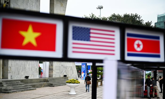 People walk past pictures of Vietnam, US and North Korean flags in Hanoi on Feb. 25, 2019, ahead of the second US-North Korea summit. (JEWEL SAMAD/AFP/Getty Images)