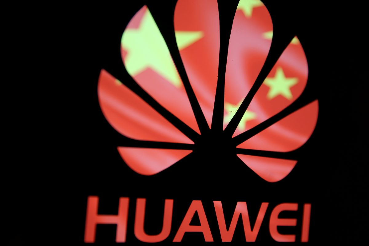 A Huawei logo is seen in front of the Chinese Communist Party flag