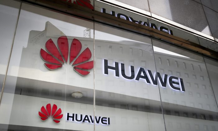 The logos of Huawei are displayed at it retail shop window reflecting the Ministry of Foreign Affairs office in Beijing on Jan. 29, 2019. (Andy Wong/AP)