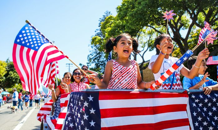 People wave American flags as they ride through the Fourth of July Parade in Alameda, Calif., on Jul. 4, 2016. (Gabrielle Lurie/AFP/Getty Images)