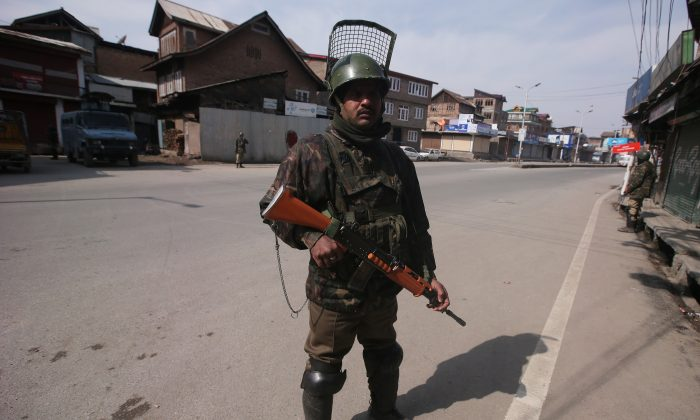 Indian Central Reserve Police Force (CRPF) personnel stand guard in front of closed shops during restrictions after Kashmiri separatist called for shutdown to protest the arrest of their leaders in Srinagar Feb. 24, 2019. (Danish Ismail/Reuters)