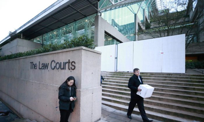 People stand outside the British Columbia Supreme Courthouse during a break in proceedings while attending the bail hearing for Huawei Technologies Chief Financial Officer Meng Wanzhou in Vancouver, Canada on Dec. 7, 2018. (Jeff Vinnick/Getty Images)