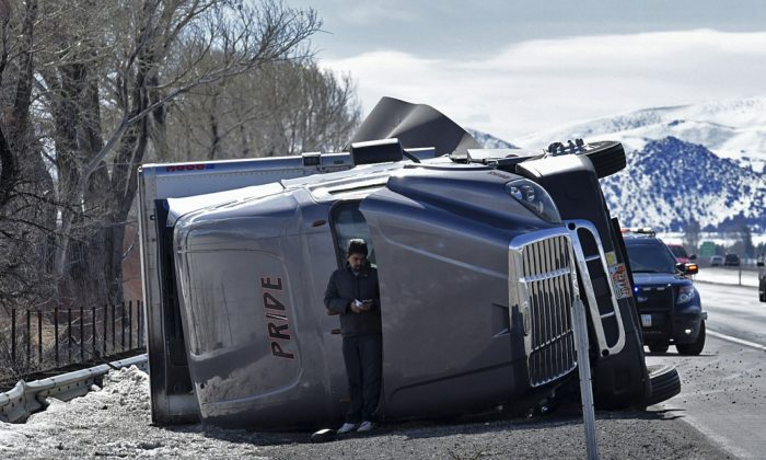 An unidentified man uses a rolled over high profile vehicle to shield himself from the wind on the Interstate 580 south of Reno, Nev., on Feb 25, 2019. Winds gusting up to 80 mph toppled trucks, downed power lines and temporarily closed part of a highway south of Reno. (Andy Barron/Reno Gazette-Journal via AP)