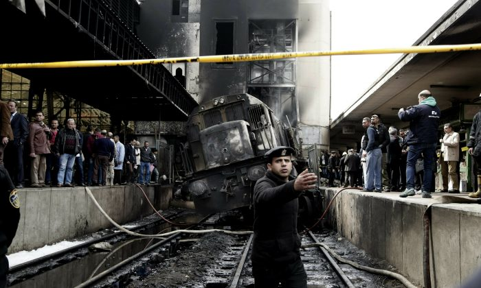 Policemen stand guard in front of a damaged train inside Ramsis train station in Cairo, Egypt, on Feb. 27, 2019. (Nariman El-Mofty/AP)