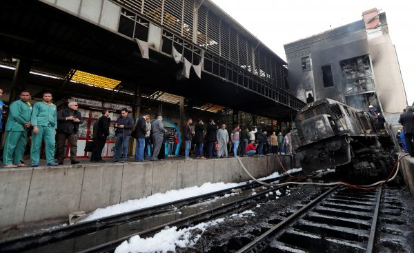 People gather at the main train station after a fire caused deaths and injuries, in Cairo