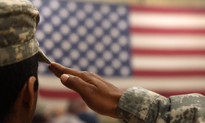A soldier salutes the flag during a ceremony for troops at Fort Carson on Colorado on June 15, 2011. (John Moore/Getty Images)