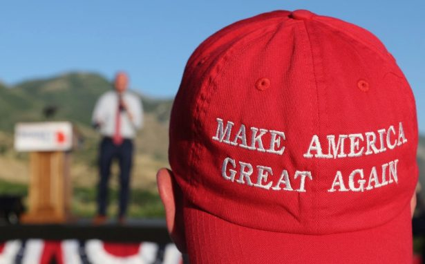"""A man listens to a speaker as he wears a """"Make America Great Again"""" hat at an election party in Orem, Utah, on June 26, 2018. (George Frey/Getty Images)"""