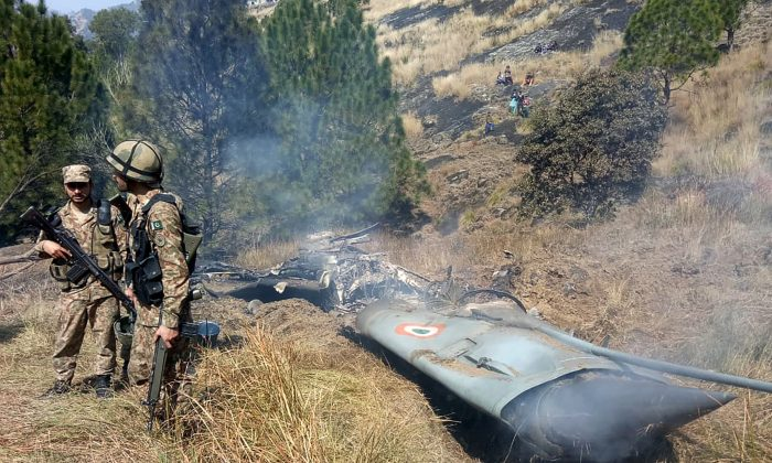 Pakistani soldiers stand next to what Pakistan says is the wreckage of an Indian fighter jet shot down in Pakistan controled Kashmir at Somani area in Bhimbar district near the Line of Control on Feb. 27, 2019. (STR/AFP/Getty Images)