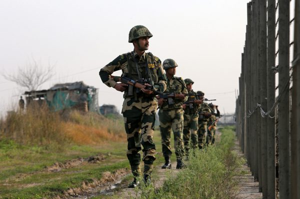 India's Border Security Force soldiers patrol along the fenced border with Pakistan in Ranbir Singh Pura sector