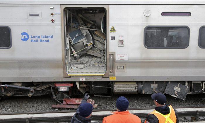 Emergency personnel look over a train that derailed after striking a vehicle in Westbury, N.Y., on Feb. 27, 2019. (Seth Wenig/AP Photo)