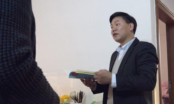 Zhang Zhiru, a prominent Shenzhen-based activist, holds a book before an interview in Guangzhou, Guangdong Province on Jan. 20, 2015. (Alexandra Harney/Reuters)