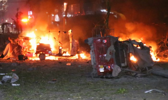 Shells of vehicles burn outside the Maka Al-Mukarama hotel in the Somalia capital, Mogadishu, on Feb. 28, 2019, after a car bomb exploded, killing at least five people and wounding 25 others. (Abdirazak Hussein Farah/AFP/Getty Images)