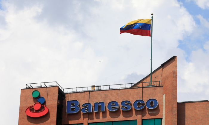 A Venezuelan flag waves above the corporate logo of Banesco bank at one of their office complexes in Caracas, Venezuela May 2, 2018. REUTERS/Marco Bello
