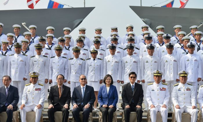 "Taiwan's President Tsai Ing-Wen (C in blue jacket) and assembled naval personnel take part in a ceremony to commission two Perry-class guided missile frigates from the US into the Taiwan Navy, in the southern port of Kaohsiung on Nov. 8, 2018. President Tsai Ing-wen vowed on Nov. 8 that Taiwan would not ""concede one step"" in defending itself as she inaugurated two frigates bought from the US aimed at boosting the island's naval capabilities against China threats. (Chris Stowers/AFP/Getty Images)"