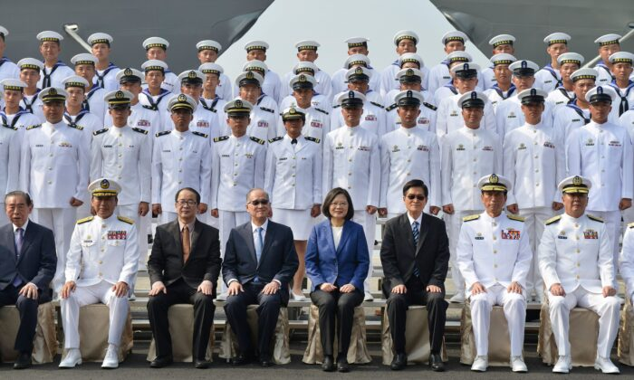 """Taiwan's President Tsai Ing-Wen (C in blue jacket) and assembled naval personnel take part in a ceremony to commission two Perry-class guided missile frigates from the US into the Taiwan Navy, in the southern port of Kaohsiung on Nov. 8, 2018. President Tsai Ing-wen vowed on Nov. 8 that Taiwan would not """"concede one step"""" in defending itself as she inaugurated two frigates bought from the US aimed at boosting the island's naval capabilities against China threats. (Chris Stowers/AFP/Getty Images)"""