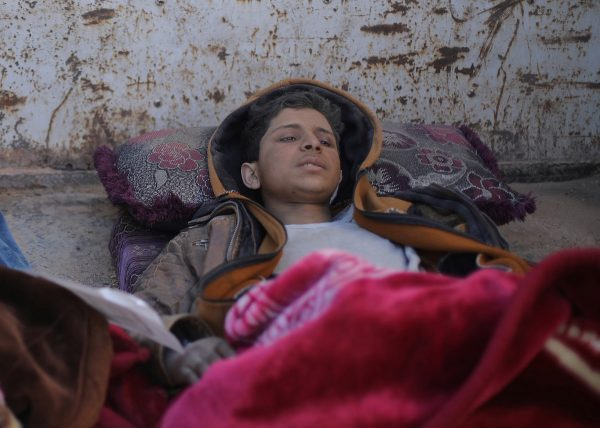 Hareth Najem, an Iraqi orphan lies under a blanket in a truck,