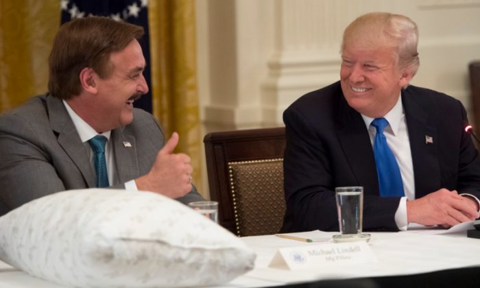 President Donald Trump shakes hands with Mike Lindell (L), founder of My Pillow, during a Made in America event with U.S. manufacturers in the East Room of the White House in Washington, on July 19, 2017. (Saul Loeb/AFP/Getty Images)
