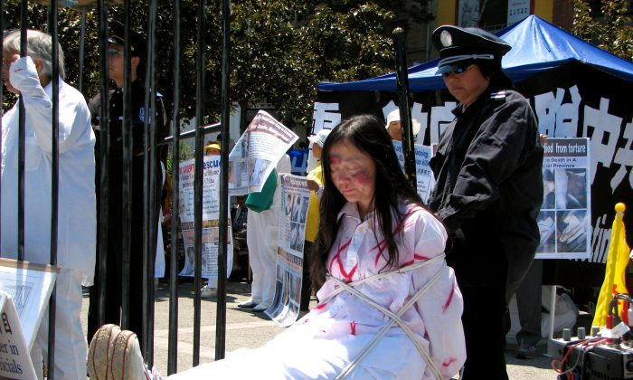 A re-enactment of a female Falun Gong practitioner being tortured. (Minghui.org)