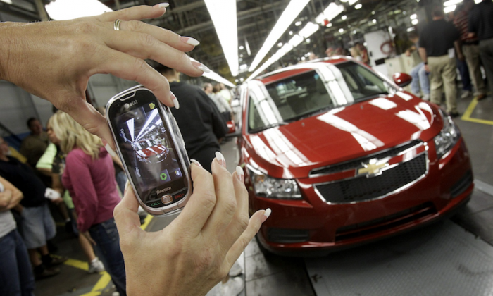 An auto worker takes a picture of the first Chevrolet Cruze compact sedan to come off the assembly line at a ceremony inside the GM factory in Lordstown, Ohio. On Sept. 8, 2010. (AP Photo/Amy Sancetta)