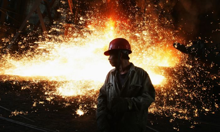 A worker with molten iron flowing up in the iron-smelting workshop at the Chengde Steel Plant in Chengde City, Hebei Province, China on October 11, 2007. (Feng Li/Getty Images)